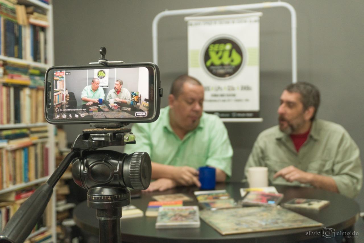 O escritor Paulo Roberto Andel e o jornalista Affonso Nunes, durante a live-piloto do vlog, gravada ao vico no Sebo X. Crédito: Silvio Almeida